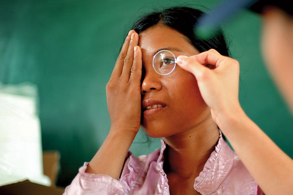 Patient looks through lens to determine eyeglass prescription during 2013 Operation Pacific Angel, Dong Hoi, Quang Binh Province, Vietnam (U.S. Air Force/Sara Csurilla)