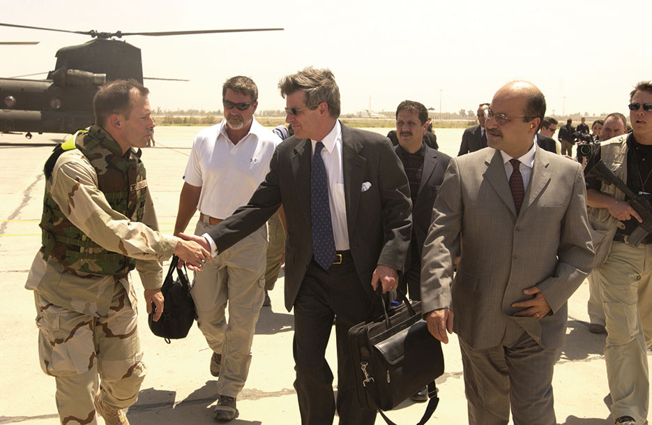 Before making his final departure from Iraq on June 28, 2004, Ambassador L. Paul Bremer shakes hands with U.S. Servicemember while he and Iraqi Deputy Prime Minister Barham Saleh walk to Baghdad International Airport (U.S. Air Force/D. Myles Cullen)