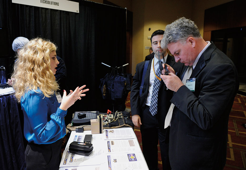 Dylan Ottman, from Office of Naval Research (ONR) Tech Solutions program, explains technology behind Fast-Tint Protective Eyewear during ONR 2012 Science and Technology Partnership Conference, Arlington, Virginia (U.S. Navy/John F. Williams)