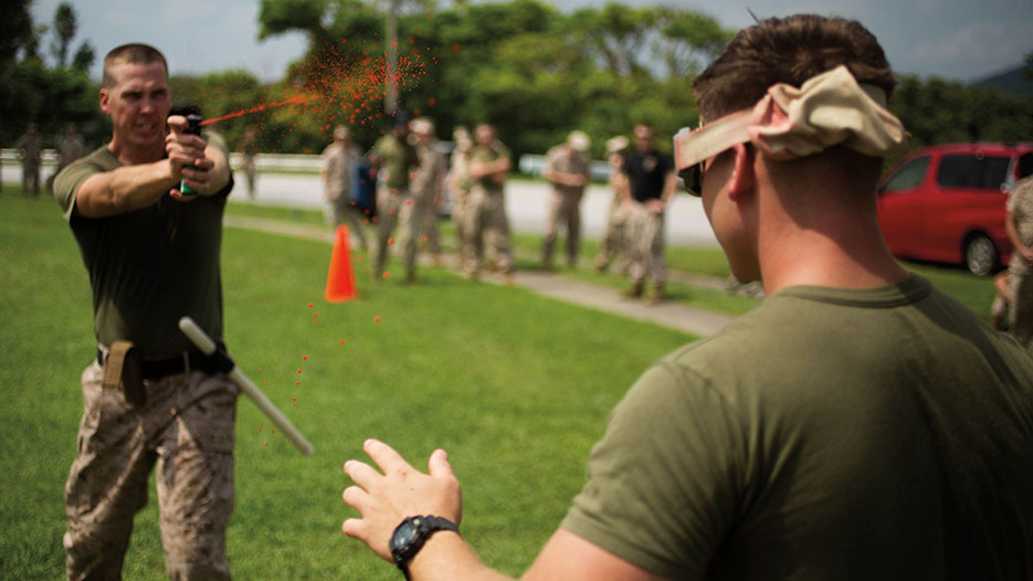 Instructor administers OC spray during OC Spray Performance Evaluation Course, part of Non-Lethal Weapons Instructor Course, on Camp Hansen, Okinawa, Japan, August 2015 (U.S. Marine Corps/Thor Larson)