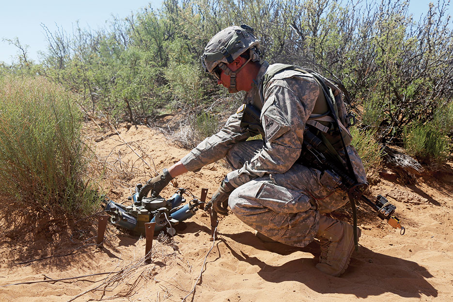 Soldier adjusts M7 Spider Networked Munitions during Network Integration Evaluation 16.2 at training village Kamal Jabul, Fort Bliss, Texas, May 2016 (U.S. Army/Chenee' Brooks)