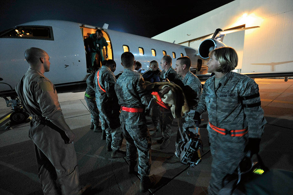 Airmen from 86th Aeromedical Evacuation Squadron and Critical Care Air Transport team from Landstuhl Regional Medical Center load wounded Libyan fighter onto civilian aircraft for transport to local German hospital, October 29, 2011, Ramstein Air Base, Germany (U.S. Air Force/Chenzira Mallory)