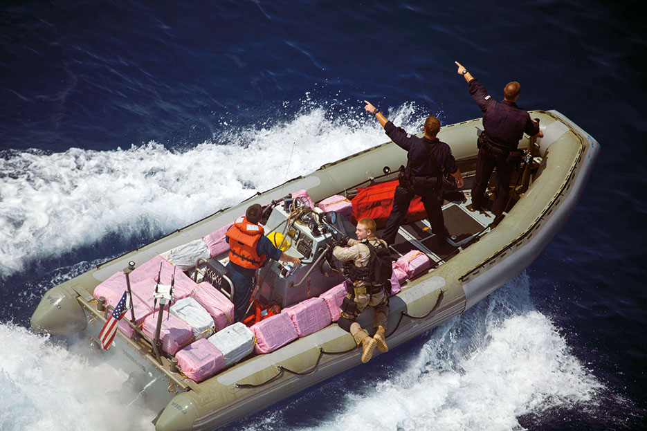 Navy and Coast Guard personnel assigned to guided-missile frigate USS Elrod signal toward narcotics bales, April 21, 2012, during recovery operations in Caribbean Sea (U.S. Army/Andy Barrera)