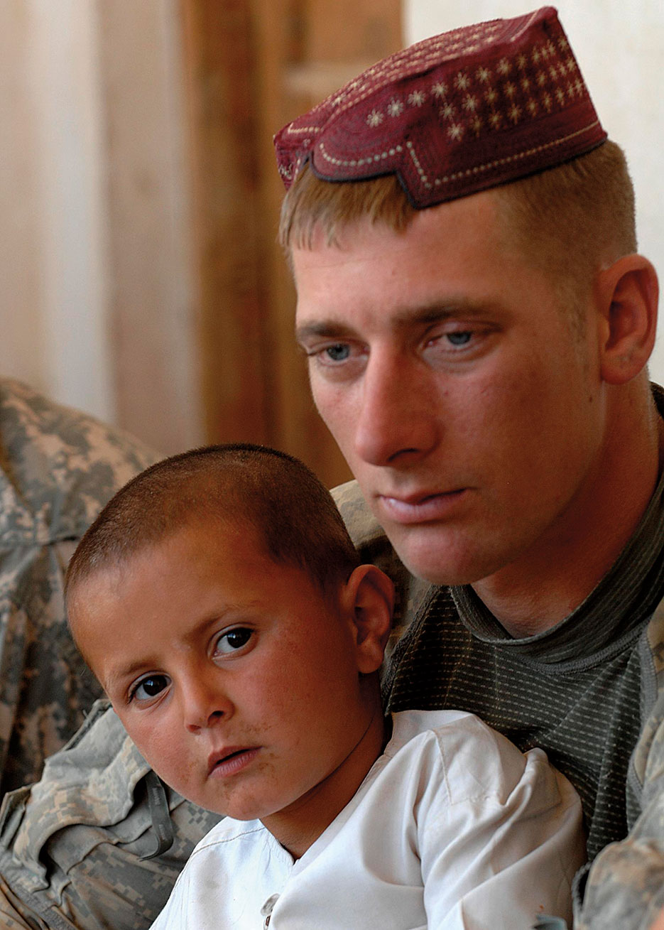Soldier holds Afghan child and wears Kandahari hat to show solidarity during key leader meeting in Koshab Village near Kandahar Air Field, Afghanistan (U.S. Army/Stephen Schester)