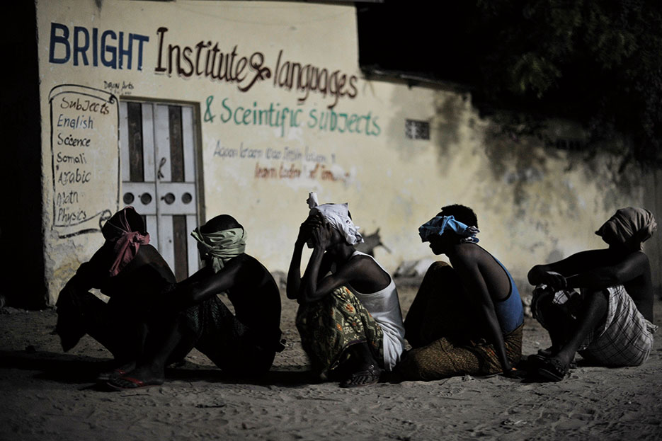 Suspected al Shabab militants wait to be taken away for interrogation during joint night operation between Somali security services and African Union Mission in Somalia forces in Mogadishu, Somalia, May 4, 2014 (Courtesy UN Photo/Tobin Jones)