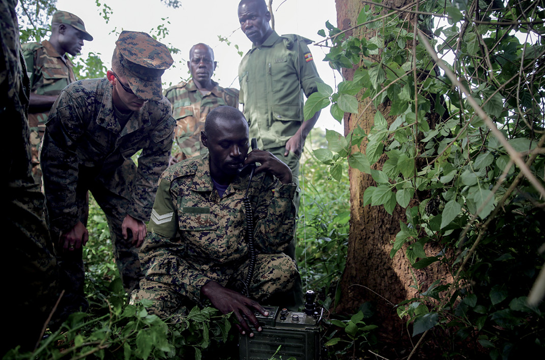 U.S. Marine assigned to Special Purpose Marine Air-Ground Task Force Crisis Response–Africa watches as Ugandan soldier uses radio to relay messages, Camp Singo, Uganda, November 17, 2016 (U.S. Marine Corps/Alexander Mitchell)