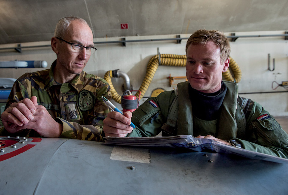 Dutch crew chief with 322nd Squadron (left) looks over flight records with U.S. Air Force Exchange Pilot at Leeuwarden Air Base, Netherlands, during NATO air forces' Frisian Flag training exercise, March 27, 2017 (U.S. Air Force/Brian Ferguson)