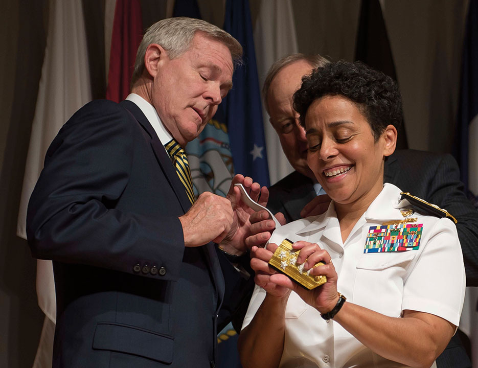 Admiral Michelle Howard lends a hand to Secretary of the Navy Ray Mabus as he and Wayne Cowles, Howard's husband, put four-star shoulder boards on her Service white uniform during promotion ceremony at the Women in Military Service for America Memorial. Howard is the first woman to be promoted to the rank of admiral in the history of the Navy (U.S. Navy/Peter D. Lawlor)