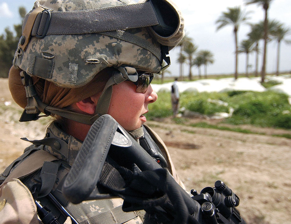 Sergeant Ashley Hort, USA, keeps weapon at ready as she provides security for fellow Soldiers during raid in Al Haswah, Iraq, March 2007 (DOD/Olanrewaju Akinwunmi)