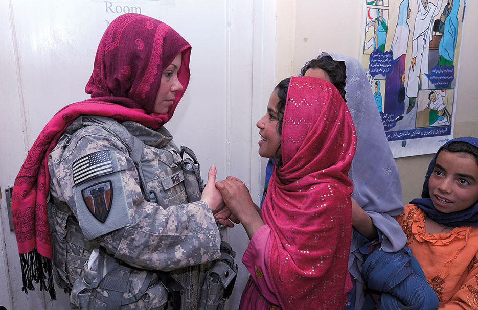 Specialist Courtney Wade, USA, a combat medic with the 176<sup>th</sup> Engineer Brigade, listens to Afghan girls during first women's shura at Urgun District hospital, April 2011 (U.S. Air Forces Central Command/Stacia Zachary)