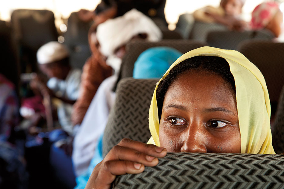Internally displaced persons ride bus to return from camp in Aramba to their home in Sehjanna, near Kutum, North Darfur (United Nations)