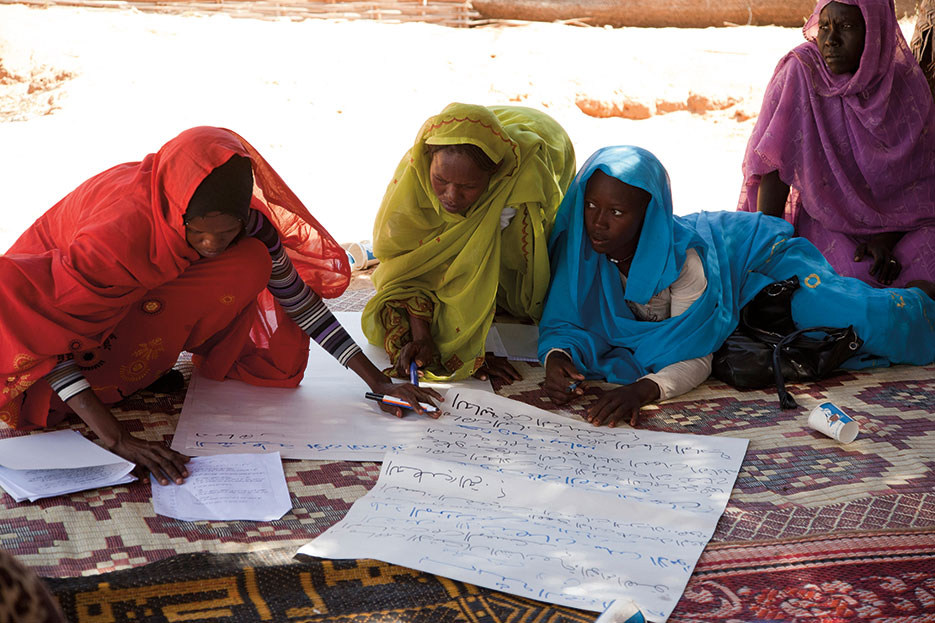 Women in Darfur's Zam Zam camp for internally displaced persons work on recommendations during forum organized to raise awareness of issues related to gender-based violence, December 2012 (United Nations/Sojoud Elgarrai)