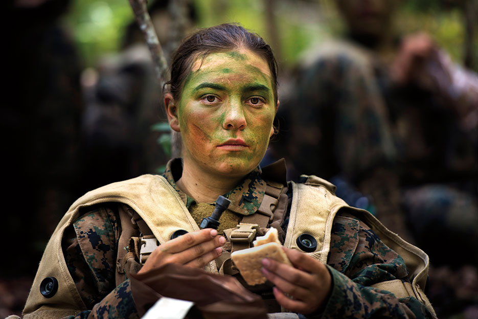 Private First Class Julia Carroll, one of the first three women to graduate from Infantry Training Battalion, eats small meal after 6-hour patrol near Camp Geiger, NC, October 2013 (U.S. Marine Corps/Tyler L. Main)