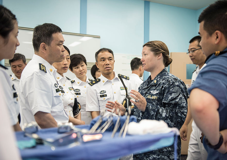 Lieutenant Jessica Naranjo, USN, speaks to People's Liberation Army Navy medical personnel from hospital ship <i>Peace Ark</i> (T-AH 866) during tour of Military Sealift Command hospital ship USNS <i>Mercy</i> (T-AH 19) (U.S. Navy/Justin W. Galvin)