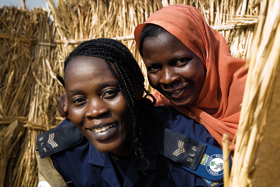 Hawa Mamoh (left), a Sierra Leonean officer with African Union–United Nations Hybrid Operation in Darfur, with Zara Adam, one of the displaced at Zam Zam internally displaced persons camp near El Fasher, North Darfur, Sudan (United Nations/Albert González Farran)