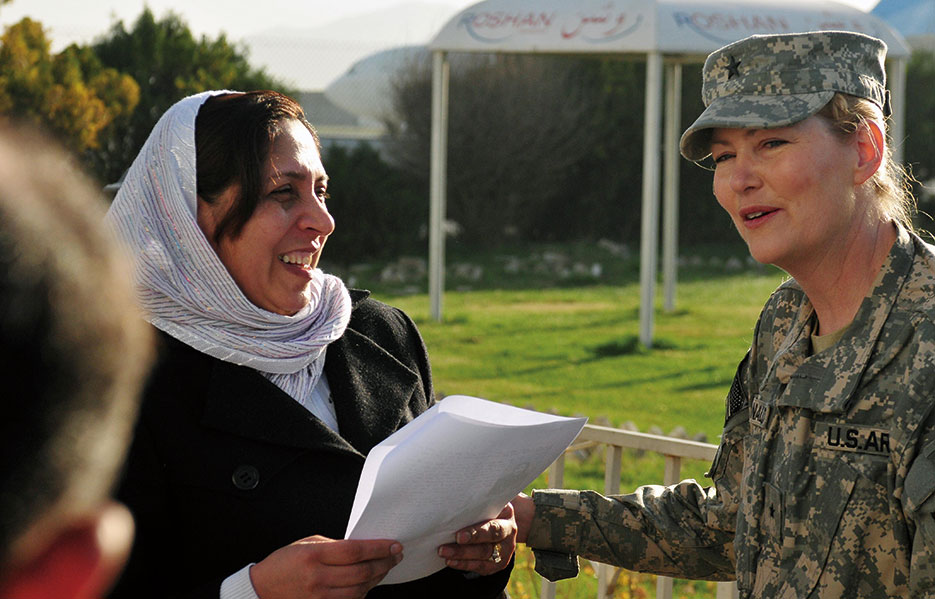 Colonel Shafiqa Quarashi, Afghan National Army, greeted by Brigadier General Anne F. Macdonald, assistant commanding general, Afghan National Police Development, Combined Security Transition Command–Afghanistan, upon Quarashi's return from the United States where she received a 2010 International Woman of Courage award from Secretary of State Hillary Rodham Clinton (U.S. Navy/David Quillen)